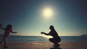 Petite fille courant vers sa mère sur le bord de la mer au lever de soleil Famille heureux banque de vidéos