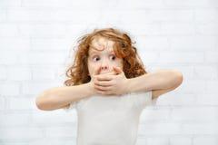Petite fille couvrant sa bouche de ses mains Étonné ou cicatrice Photographie stock
