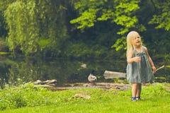 Petite fille curieuse marchant à l'étang en été Images libres de droits