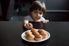 Petite fille curieuse mignonne atteignant des petits pains sur la table image libre de droits