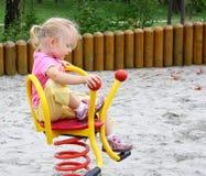 Petite fille débarrassant l'oscillation de source Photos libres de droits