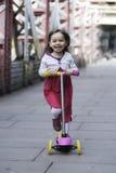 Petite fille débarrassant le scooter images stock