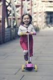 Petite fille débarrassant le scooter photos libres de droits