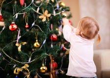 Petite fille décorant l'arbre de Noël Photographie stock libre de droits