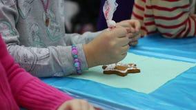 Petite fille décorant le pain d'épice avec le lustre de couleur, métier de boulangerie, fait main banque de vidéos