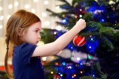 Petite fille décorant un arbre de Noël Images libres de droits