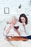 Petite-fille délicieuse appréciant le petit déjeuner avec la grand-mère retirée à la maison Photographie stock libre de droits