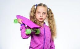 Petite fille détendant après patinage Portrait de petite fille avec la planche à roulettes pourpre Enfant de hippie avec le panne photographie stock libre de droits