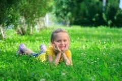 Petite fille détendant sur l'herbe Images stock