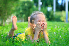 Petite fille détendant sur l'herbe Photo stock