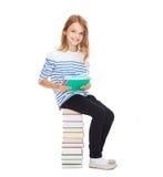 Petite fille d'étudiant s'asseyant sur la pile de livres Photo libre de droits