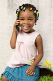 Petite fille d'afro-américain à l'aide d'un téléphone portable Photographie stock