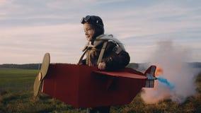 Petite fille d'aviateur courant à la forêt et au champ de coucher du soleil dans l'avion de carton d'amusement avec de la fumée d clips vidéos