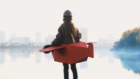 Petite fille d'aviateur de vue arrière observant le panorama brumeux de ville de lac dans le mouvement lent d'avion de carton et  clips vidéos
