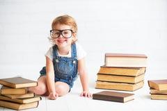 Petite fille d'enfant avec la lecture en verre livres photos libres de droits
