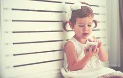 Petite fille d'enfant avec le smartphone de téléphone Photographie stock