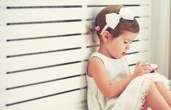 Petite fille d'enfant avec le smartphone de téléphone Photo libre de droits