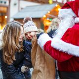 Petite fille d'enfant en bas âge avec la mère sur le marché de Noël Image stock