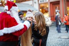 Petite fille d'enfant en bas âge avec la mère sur le marché de Noël Photographie stock libre de droits