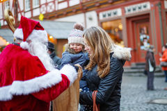 Petite fille d'enfant en bas âge avec la mère sur le marché de Noël Photographie stock