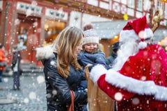 Petite fille d'enfant en bas âge avec la mère sur le marché de Noël Images libres de droits