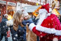 Petite fille d'enfant en bas âge avec la mère sur le marché de Noël Photos stock