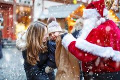 Petite fille d'enfant en bas âge avec la mère sur le marché de Noël Image libre de droits