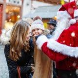 Petite fille d'enfant en bas âge avec la mère sur le marché de Noël Photos libres de droits