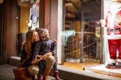 Petite fille d'enfant en bas âge avec la mère sur le marché de Noël Photo libre de droits