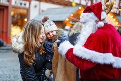 Petite fille d'enfant en bas âge avec la mère sur le marché de Noël Images stock