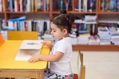 Petite fille d'enfant heureux lisant un livre images stock