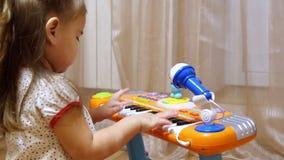 Petite fille d'enfant jouant sur un piano de jouet clips vidéos