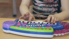 Petite fille d'enfant jouant sur un piano de jouet banque de vidéos
