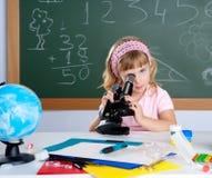 Petite fille d'enfants à l'école avec le microscope photographie stock libre de droits