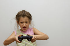 Petite fille d'enfants tenant le jeu vidéo heureux de jeu de manette Image stock