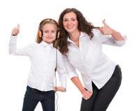 Petite fille dans des écouteurs écoutant la musique et la mère Image libre de droits