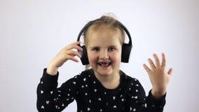 Petite fille dans des écouteurs dansant et chantant banque de vidéos