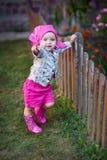 Petite fille dans des chaussures roses près de la barrière photos stock