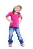 Petite fille dans des jeans sur le fond blanc photographie stock
