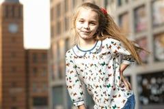 Petite fille dans des lunettes de soleil posant sur le fond de bâtiment Image libre de droits