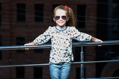 Petite fille dans des lunettes de soleil posant sur le fond de bâtiment Photos libres de droits