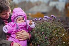 Petite fille dans des mains du père Photographie stock libre de droits