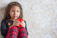 Petite fille dans des pyjamas de Noël avec une tasse de cacao, thé dans le lit Photo libre de droits