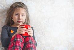 Petite fille dans des pyjamas de Noël avec une tasse de cacao, thé dans le lit Images libres de droits