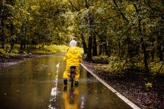 Petite fille dans des vêtements imperméables jaunes sur le vélo Photos libres de droits