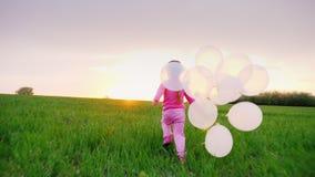 Petite fille dans des vêtements roses avec des ballons Je joue le long du pré vert vers le coucher du soleil Rêve du ` s d'enfant clips vidéos