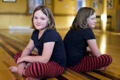 Petite fille dans des vêtements sport se reposant en tailleur sur le plancher d'un studio de danse images stock