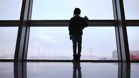 Petite fille dans l'aéroport près de la grande fenêtre tandis qu'attente l'embarquement banque de vidéos