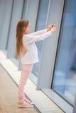 Petite fille dans l'aéroport près de la grande fenêtre tandis qu'attente l'embarquement Photo libre de droits