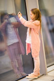Petite fille dans l'aéroport près de la grande fenêtre tandis qu'attente l'embarquement Photo stock